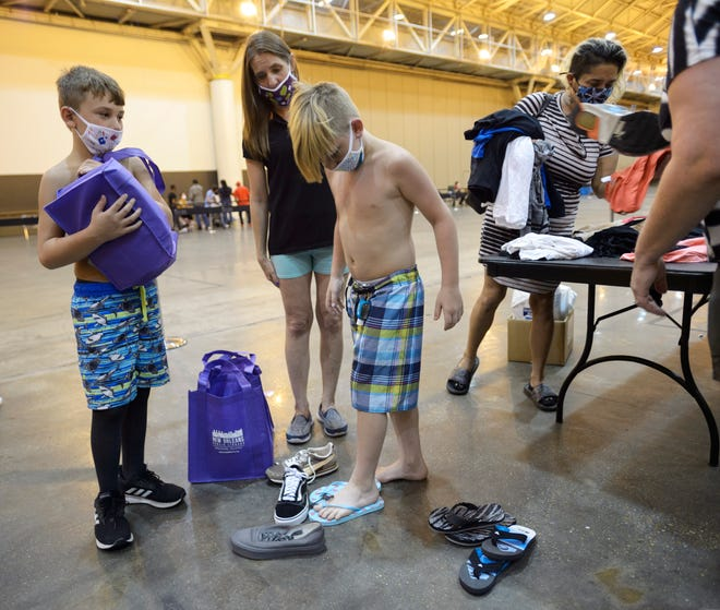 Evacuees from Hurricane Laura Bentley White, 9, center, tries on shoes with Chris Cormier, 10, left, and Angela Cormier while visiting an aid center at the Ernest N. Morial Convention set up by the Federal Emergency Management Agency and Governor's Office of Homeland Security & Emergency Management in New Orleans.