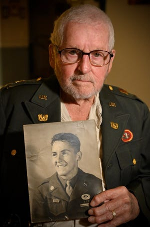 John Bellefontaine poses with a photo of himself in the Army.