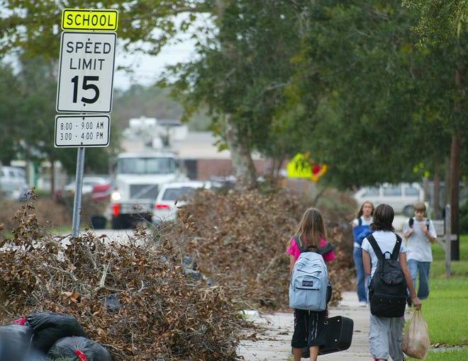 Students walk past piles of debris left by Hurricane Frances in Ormond Beach on Sept. 14, 2004.