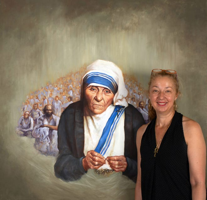 """Artist Cecile Houel is shown with her portrait of Mother Teresa, the 1979 Nobel Peace Prize Laureate. Houel is working on a ten-year project to paint all 107 Laureates to date, and is showing her completed works at four Quad Cities locations during September, with a reception Friday at the Beréskin Art Gallery & Academy in Bettendorf. A tour """"passport"""" and complete information is available at bereskinartgallery.com."""