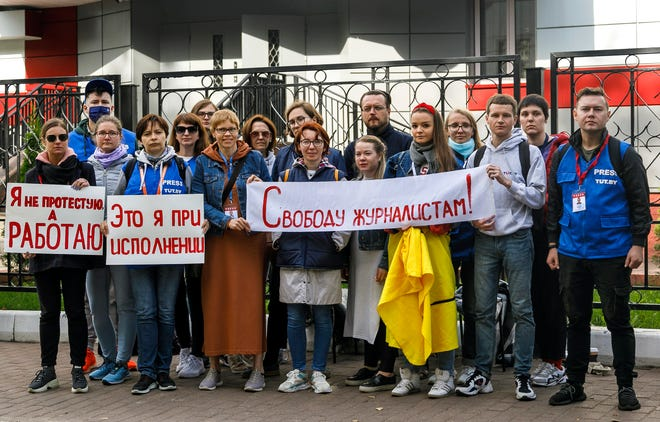 "Journalists of Belarusian TUT.BY media outlet hold banners reading ""I don't protest but work"", ""This is me at work"", ""Freedom for journalists!"", from left to right, as they stand in front of police station in Minsk, Belarus, on Wednesday. More than a dozen Belarusian journalists went out on Wednesday night to the building of the district police department to protest against the detention of their colleagues covering the dispersal of a student rally in the Belarusian capital."
