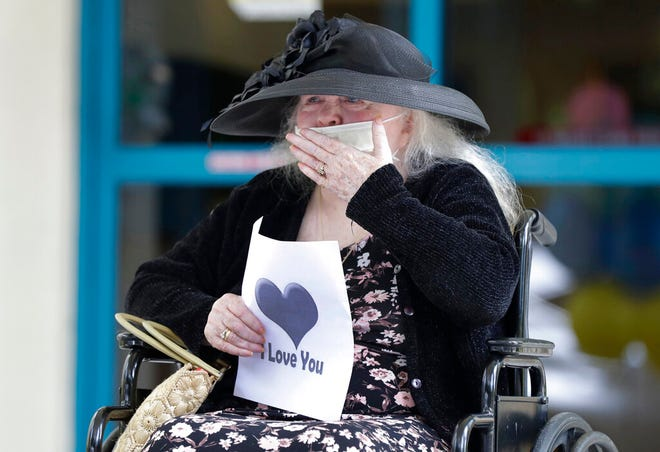FILE - In this July 17, 2020, file photo, Margaret Choinacki, 87, who has no other family members left because her husband and daughter have died, blows kisses to her friend Frances Reaves during a drive-by visit at Miami Jewish Health in Miami. Floridians will soon be allowed to visit loved ones in nursing homes after nearly six months of vulnerable seniors being cut off from family as Gov. Ron DeSantis announced Tuesday, Sept. 1, 2020, that facilities could start a partial reopening.