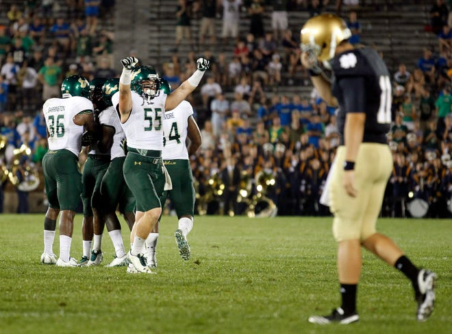 South Florida linebacker Michael Lanaris (55) celebrates an interception of Notre Dame quarterback Tommy Rees, right, late in the fourth quarter of a game in 2011 in South Bend, Indiana. South Florida won the game 23-20.