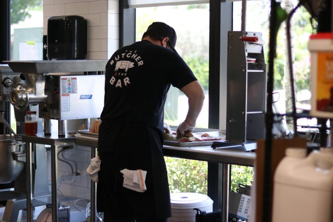 Chef Daniel Ramos prepares a porchetta to roast for sandwiches at The Butcher and the Bar in Boynton Beach. [Photo by Jupiter Compass Digital Marketing]