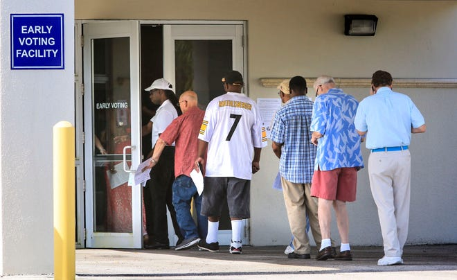 A small crowd of voters streams into the Supervisor of Elections Office on S. Military Trail in West Palm Beach as the doors open for early voting in 2014. [Lannis Waters / PalmBeachPost.com]