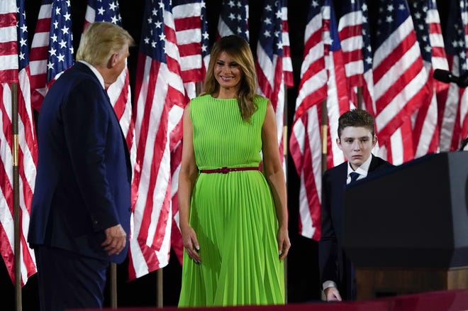 President Donald Trump appears on stage with first lady Melania Trump after he gave a speech from the South Lawn of the White House on the fourth day of the Republican National Convention, Thursday, Aug. 27, 2020, in Washington. Barron Trump is at right. [AP Photo/Alex Brandon]