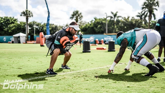 Miami Dolphins outside linebackers coach Austin Clark gets in the trenches with a player.