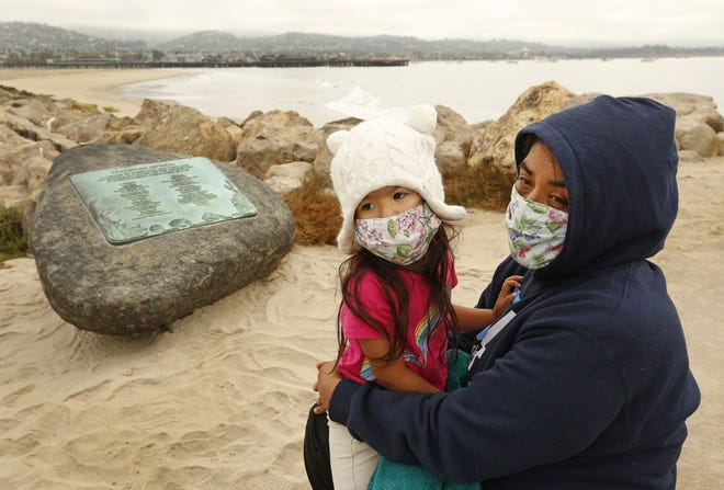 Yadira Alvarez-Peterson holds her 3-year-old daughter Renata Alvarez-Peterson close talking about her 16-year-old daughter Berenice Felipe, who was one of the 34 people who died in the Conception Boat fire one year ago today as family members with friends and officials gathered at Point Castillo at the end of Harbor Walk in the Santa Barbara Harbor where a plaque on a boulder was unveiled to memorialize the 34 lives lost in the Conception Diving Boat fire off Santa Cruz Island on the one year anniversary.
