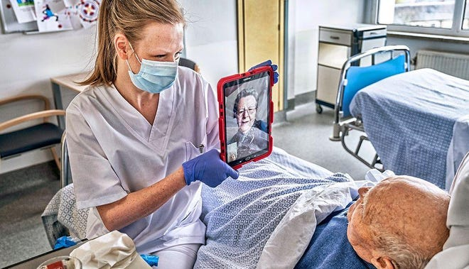 A nurse helps a nursing home resident have a virtual visit with a family member during the COVID-19 pandemic. At least 24 facilities around the state have reported 100 or more cases among residents and staff, and at least threelong-term care facilities in Missouri have seen 30 or more residents die from the virus.