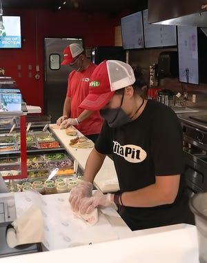 Pita Pit Co-owner Jessica Ferguson wraps up a sandwich at the new Kent restaurant.