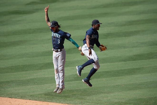 Seattle Mariners shortstop J.P. Crawford, left, and center fielder Kyle Lewis celebrate the team's 2-1 Monday win over the Los Angeles Angels in Anaheim, Calif. (AP Photo/Kyusung Gong)