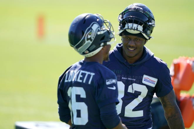 Seattle Seahawks running back Chris Carson, right, talks with wide receiver Tyler Lockett during Tuesday's practice in Renton, Wash. (AP Photo/Ted S. Warren)