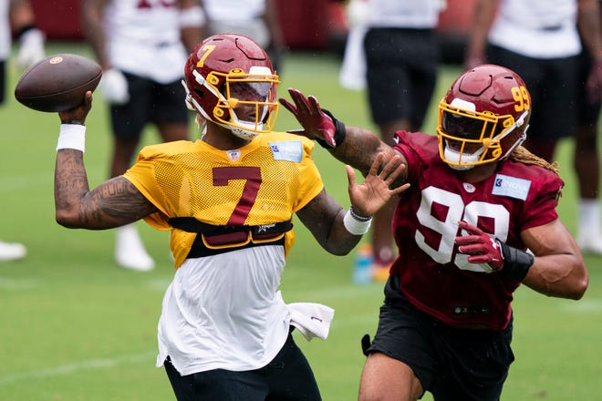 Washington quarterback Dwayne Haskins Jr. (7) passes under pressure from defensive end Chase Young during Monday's practice at FedEx Field in Washington. (AP Photo/Alex Brandon)