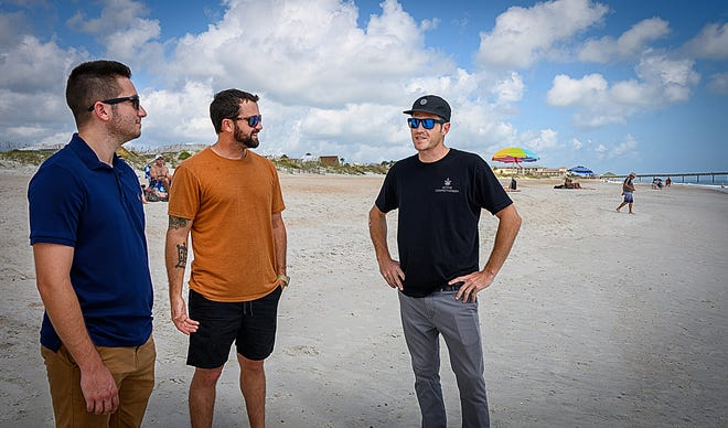 Jon Simone talks with Al Angyalfy and Pat Conner on St. Augustine Beach on Wednesday near where the two men rescued him from the water in August.