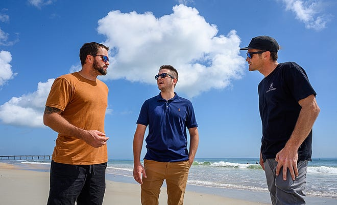 Jon Simone, center, talks with Al Angyalfy and Pat Conner on St. Augustine Beach on Wednesday near where the two men rescued him from the water in August.