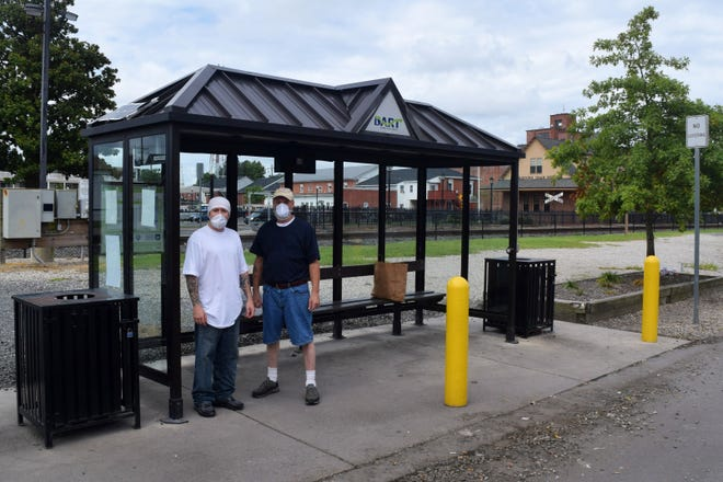 Jerry Griner of Seaford, left, and Michael Young of Smyrna, wait for a bus at the DART Georgetown Transit Hub on Railroad Avenue.