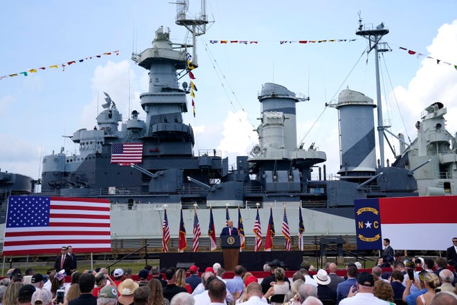 With the Battleship North Carolina in the background, President Donald Trump speaks during a ceremony to designate Wilmington as the first American World War II Heritage City on Wednesday. [AP Photo/Evan Vucci]