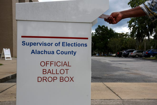 A voter puts their mail ballot in a drop box at the Alachua County Supervisor of Elections Office in Gainesville on Aug. 8.