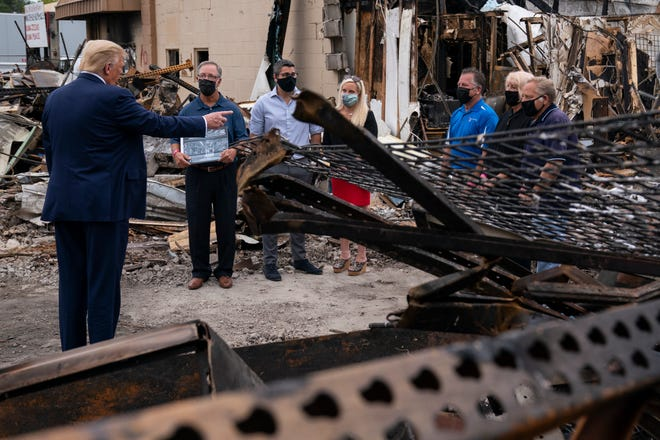 President Donald Trump speaks with business owners Tuesday as he tours an area damaged during demonstrations after a police officer shot Jacob Blake in Kenosha, Wis.