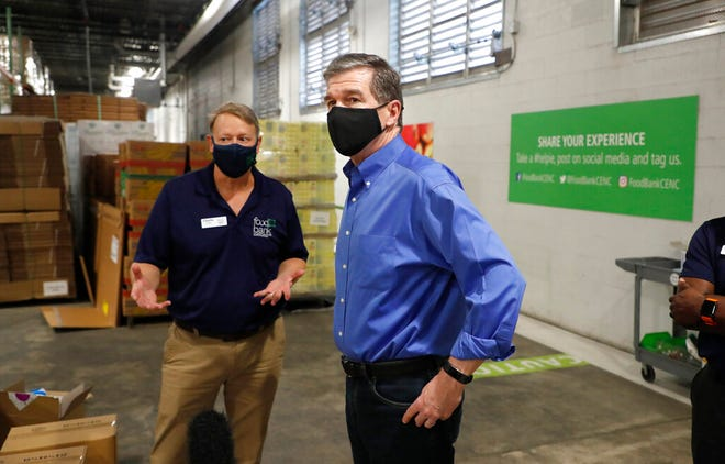 FILE - North Carolina Gov. Roy Cooper talks with Charlie Hale, vice president of Operations & Programs of the Food Bank of Central & Eastern North Carolina, during the governor's tour of the Raleigh, N.C., branch of the food bank, Thursday, Aug. 27, 2020.   Four years after he narrowly won the politically divided state carried by then-candidate Donald Trump,  Cooper now has a double-digit lead over his Republican challenger, Lt. Gov. Dan Forest. Cooper's reelection path offers clues to what will work for Southern Democrats in an election cycle that also will determine control of the White House and Congress.  (Ethan Hyman/The News & Observer via AP, File)