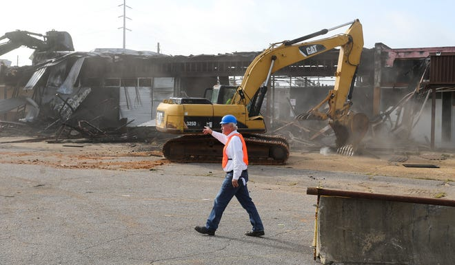 The Bar 17 property on 10th Street was demolished along with the associated strip mall Wednesday morning. Developer Stan Pate gestures as his crew works to demolish the existing structure. [Staff Photo/Gary Cosby Jr.]