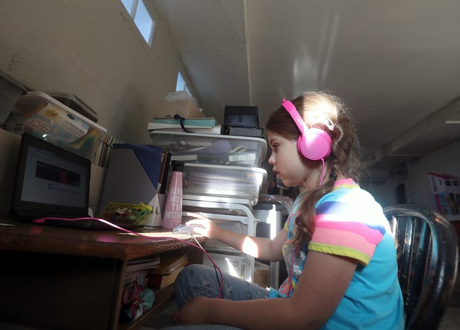 First-grader Emma Pedelaborde logs on for her first day of school, from her desk in the basement of the family's home in Bremerton on Sept. 2. A new school year has brought on challenges for school districts, which face increased costs as a result of teaching in the COVID-19 environment, as well as a larger-than-expected decrease in enrollment.