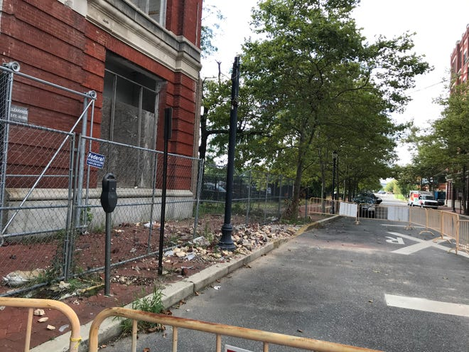 Fencing and other barriers surround an area on Front Street where bricks have fallen from the Radio Lofts building in Camden.