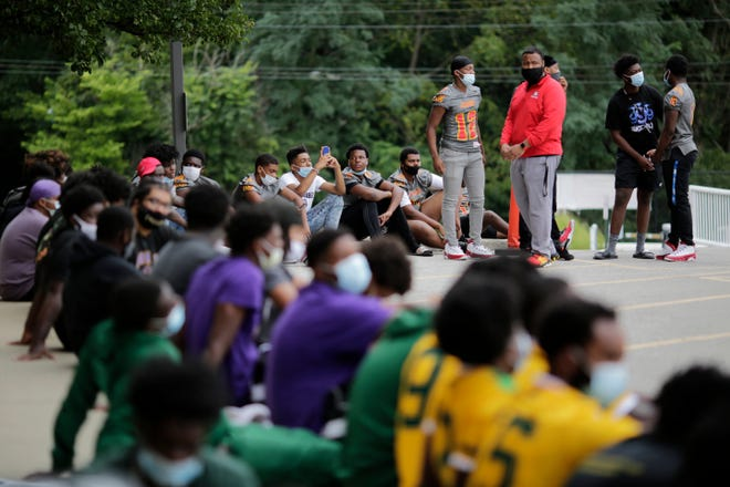 Parents and student athletes gather outside as they listen to a meeting via live stream outside of the Cincinnati Public Schools central office in the Mt. Auburn neighborhood of Cincinnati on Wednesday, Sept. 2, 2020. The board of education announced after its meeting that the district's sports programs would not resume until further notice, despite other schools in the region having begun last week.