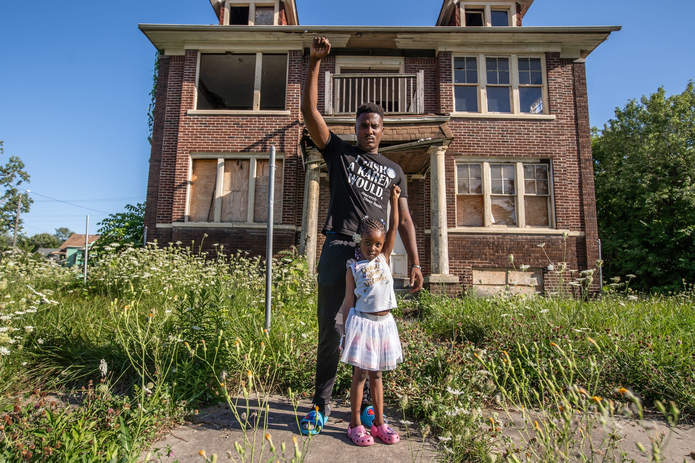 """Jae Bass, 25, of Detroit poses for a photo with his daughter Daria Bass, 5, in front of an abandoned house on Collingwood Street in Detroit on Thursday, August 20, 2020. """"I look around, I see abandoned houses. I see degradation. I see desolate areas and I think I'm finally at an age and experienced enough to understand that that is all on purpose. It just is not a lack of resources because of the lack of resources. It is a lack of resources because we are intentionally being starved of resources so that we have limited options on how to get resources which just further perpetuates crime and other things in my neighborhood. So the reason I march is because I know the only way that's gonna change is if the people come together and actually make that change happen. If this is truly a democracy, it means that the country should run off of what the needs and desires of the people are. That we need to take that power back. So we get in the streets and we take that power back,"""" Bass said. """"If you didn't think that we would be out here a hundred days, you are truly underestimating the power of this movement because we'll be out here a hundred more days and one hundred more days after that. However long it takes to get justice and truly make change that's gonna be everlasting in our city, state and country and eventually the world."""""""