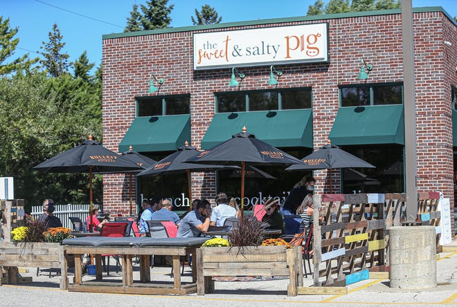 Diners sit in the new outdoor seating area at the Sweet & Salty Pig restaurant in Fond du Lac.