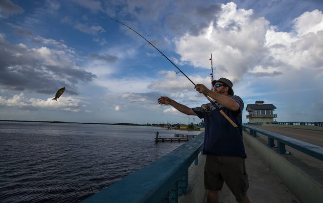 Max Rousseau, who only recently picked up fishing as a hobby, catches a small grouper off of the Matlacha Bridge.