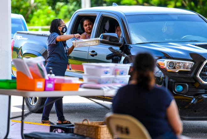 Kindergarten teacher Tarsila Muth, standing, delivers instructional material to a parent during a drive-through Grab-n-Learn distribution at Finegayan Elementary School in this Sept. 2 file photo.