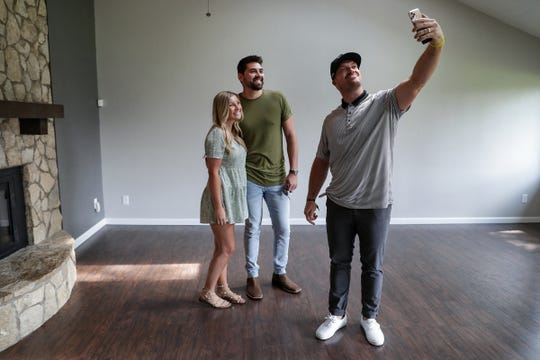 Matt Overton, former Indianapolis Colts long snapper turned F.C. Tucker Realtor, takes a selfie with Ella Hammons and Kyle Mendenhall inside their new home in Lawrence Township on Friday, Aug. 28, 2020.