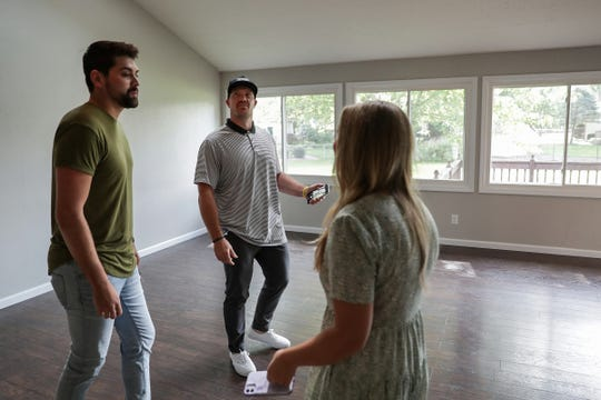 Center, Matt Overton, former Indianapolis Colts long snapper turned F.C. Tucker Realtor, walks Kyle Mendenhall and Ella Hammons through their new home in Lawrence Township, Ind., on Friday, Aug. 28, 2020.