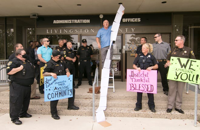 Members of the Livingston County Sheriff's Department flank Genoa Township resident Kurt Skarjune, who holds a string of sheets of paper containing messages of support for law enforcement officers, in front of the Sheriff's Department Wednesday, Sept. 2, 2020.