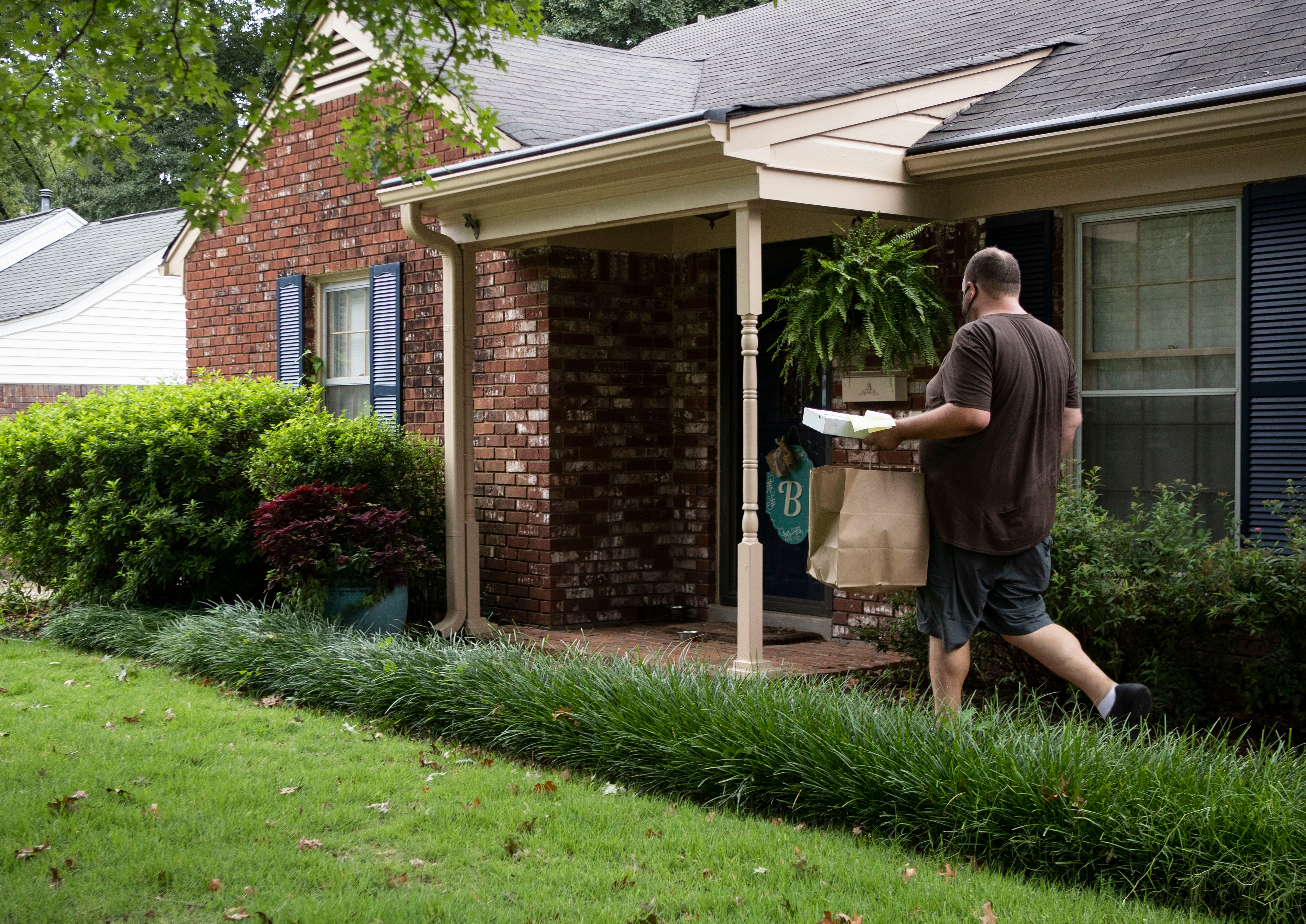 Pete and Sam's delivery driver Hunter Burkes delivers a  pizza to a customer's door during his shift in Memphis, Tenn., on Tuesday, September 1, 2020.