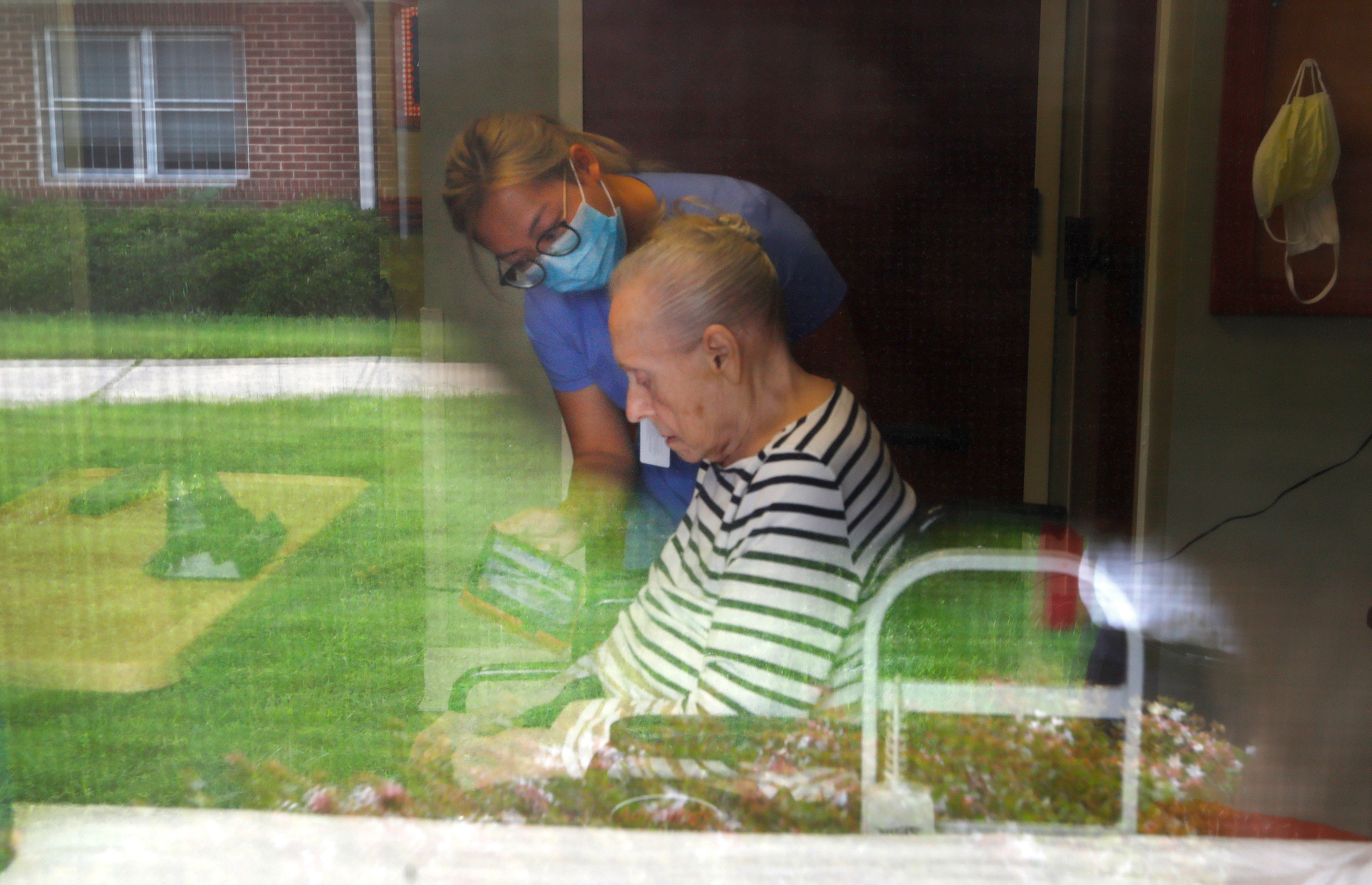 """Wei Zeng tries to alert Maureen Buchman, 89, to her daughter Maureen Perkins' calls through the window of her senior living facility just after 10am on Sept. 1, 2020. Buchman, who has dementia, doesn't respond to her daughter on this day. """"This is the first time she has been glazed, says Perkins. """"It's going to be a hard one to put behind me today."""""""
