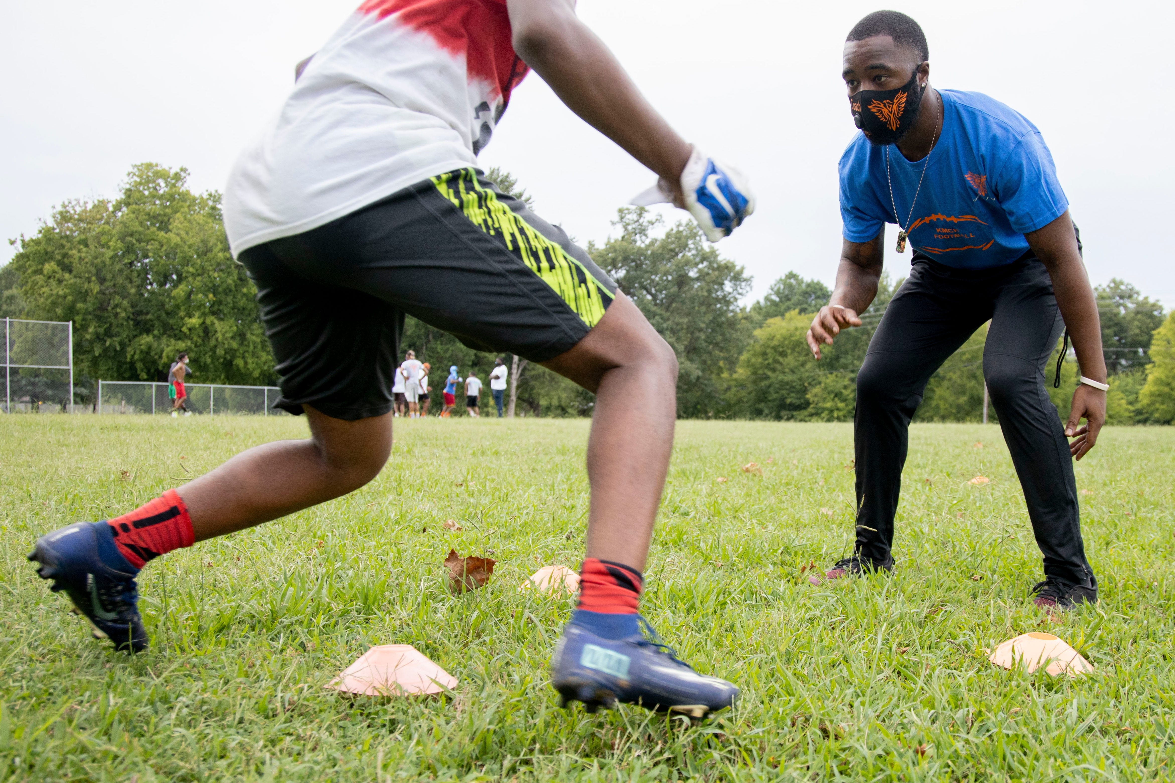 Football coach T.J. Ayers (right) guides Melikah Stokes, 14, through a conditioning drill Tuesday, Sept. 1, 2020, at KIPP Memphis Collegiate High School.