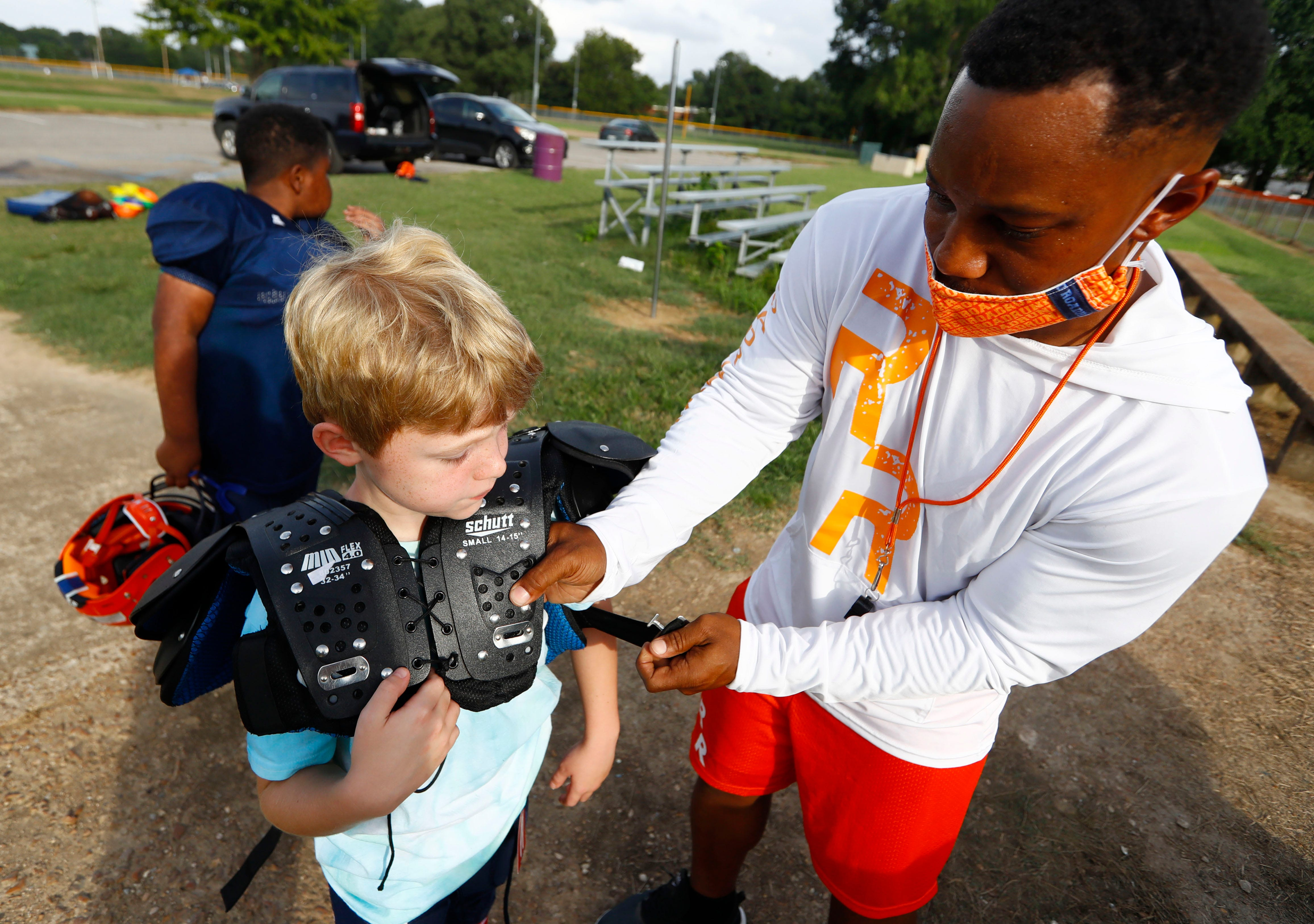 Coach Antoine Smith helps Porter Throckmorton, 8, with his pads before practice at Willow Park on Tuesday, Sept. 1 with the Mount Moriah Road Runners, a youth program created by the Sheriff's & Police Activities League of Memphis and Shelby County, a non-profit mentoring organization.