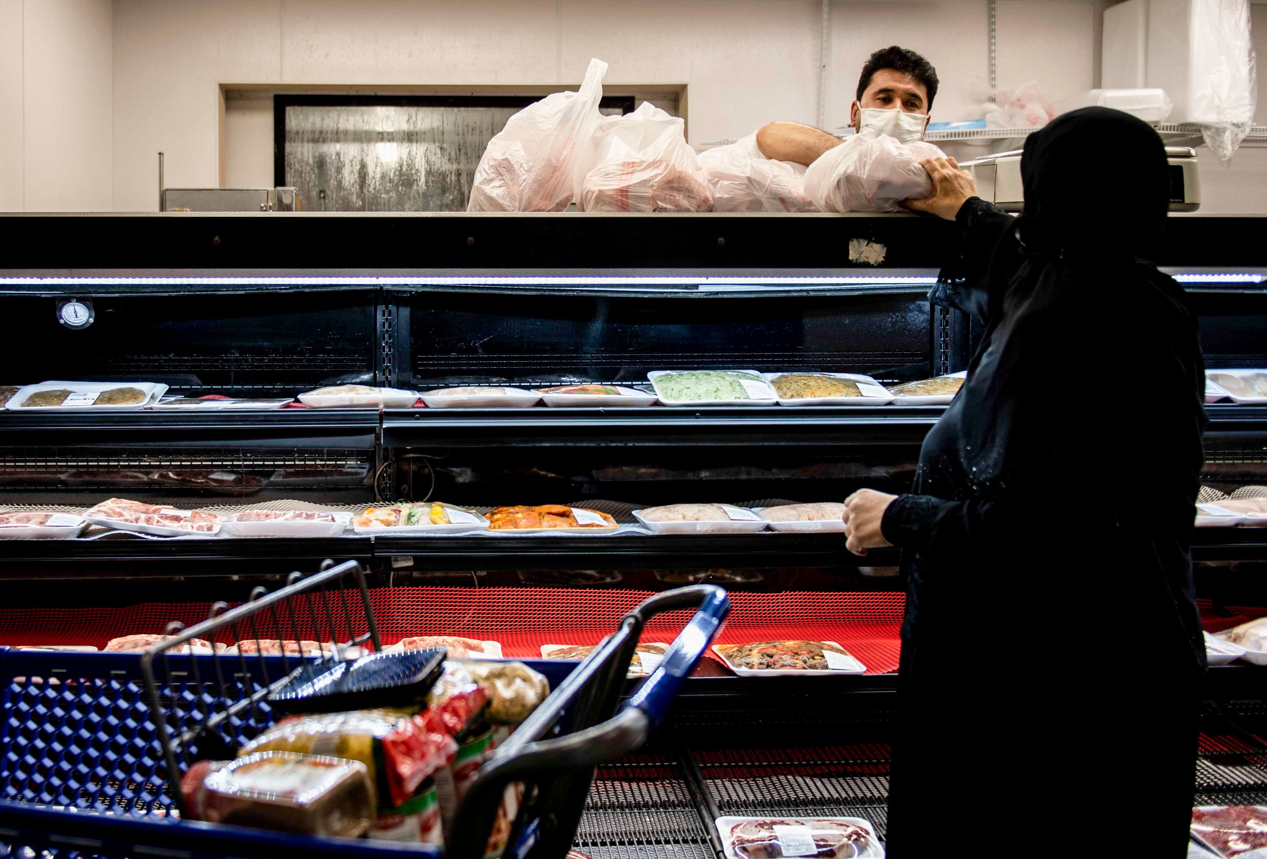 Naim Nazari passes meat to a customer at Alrahmah Mediterranean Grocery in Cordova on Tuesday, Sept. 1, 2020. The Eldahan family has owned the business for 12 years and has served their community in Memphis despite the pandemic and have provided them with essential products.