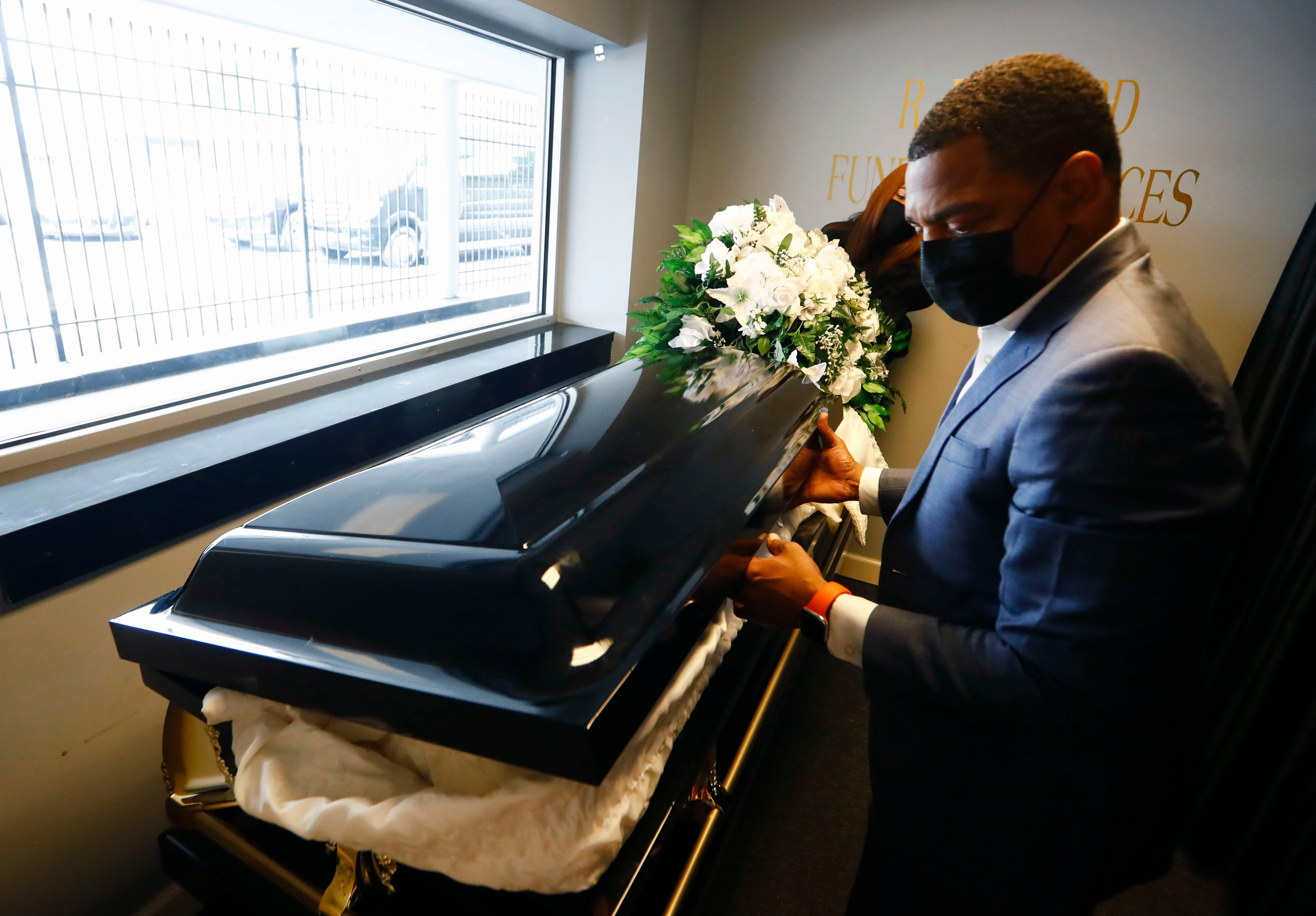 Ryan Bernard moves a casket from the funeral home's drive-thru viewing window area, which has been utilized extensively during the pandemic for socially distant celebration of life ceremonies at R Bernard Funeral Services on Sept. 1, 2020.