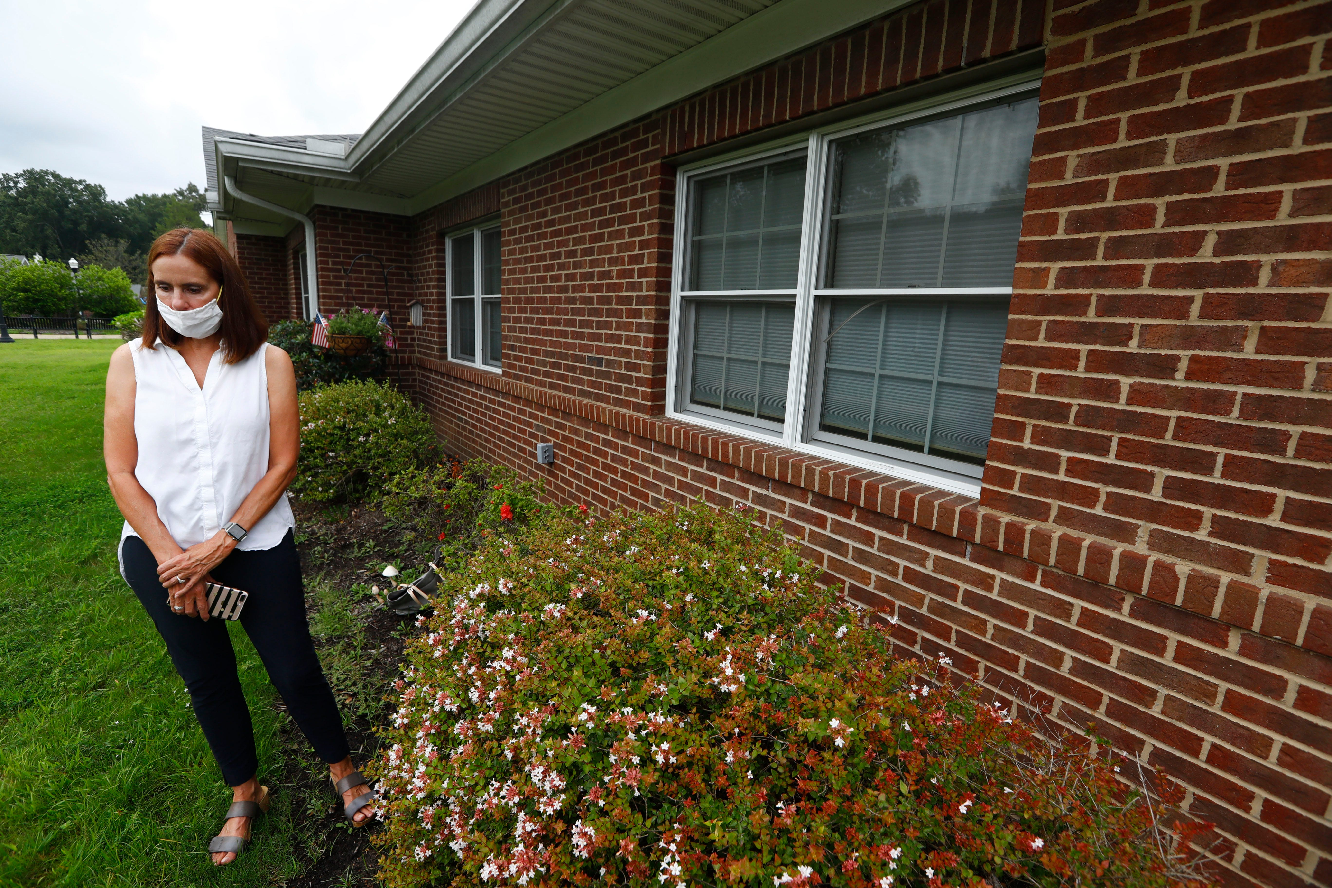 """Maureen Perkins stands outside her mother's window, Maureen Buchman, 89, at her senior living facility just after 10am on Sept. 1, 2020. Buchman, who has dementia, doesn't respond to her daughter on this day. """"This is the first time she has been glazed, says Perkins. """"It's going to be a hard one to put behind me today."""""""
