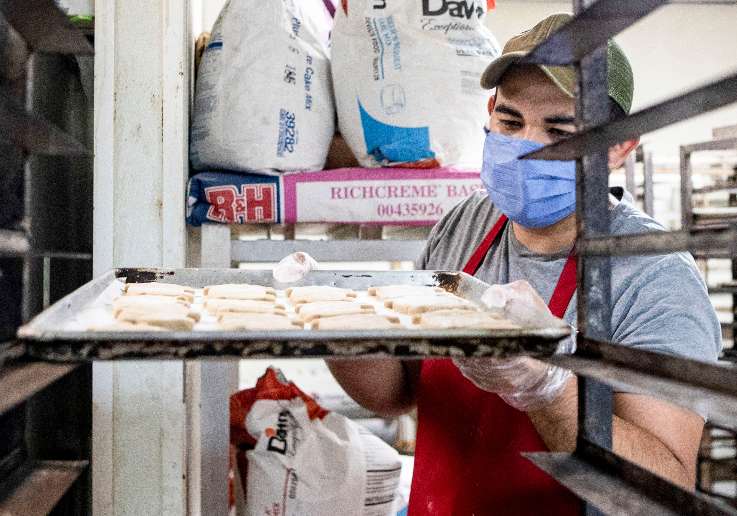 Itiel Perez places a tray of puerquitos on a transport trolley in the kitchen at Caminos de Michoacan in Memphis, Tenn., on Tuesday, September 1, 2020.
