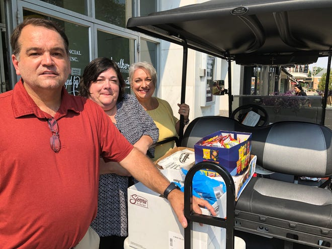 """From left, Eric Wright, Shannon Walker and Heather Stasel of St. Francis de Sales Catholic Church, get ready to take food, snacks and water to the homeless in and around downtown Newark last week. It's part of their """"golf cart ministry"""" through the church's Catholic Outreach Ministries."""