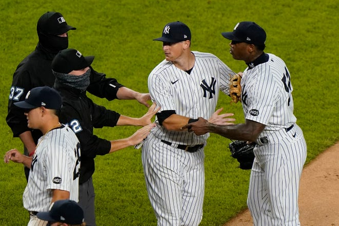 Officials and New York Yankees' DJ LeMahieu restrain New York Yankees relief pitcher Aroldis Chapman, right, after he and the Tampa Bay Rays exchanged words at the end of a baseball game, Tuesday, Sept. 1, 2020, at Yankee Stadium in New York. The incident occurred after Chapman threw a high pitch at the Rays' Michael Brosseau in the ninth inning.