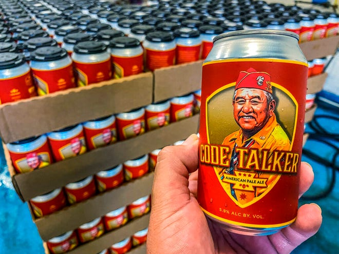 In this Aug. 14, 2020, photo courtesy of LT Goodluck, LT Goodluck holds a beer can honoring his grandfather, Navajo Code Talker John V. Goodluck at the Hellbender Brewing Co., in Washington, D.C. In honor of National Navajo Code Talkers Day the craft brewery recently rereleased its Code Talker American Pale Ale , this time in a can, drawing some rave reviews but also backlash. The beer was formulated and brewed by Goodluck in honor of his late grandfather and Navajo Code Talker John V. Goodluck.