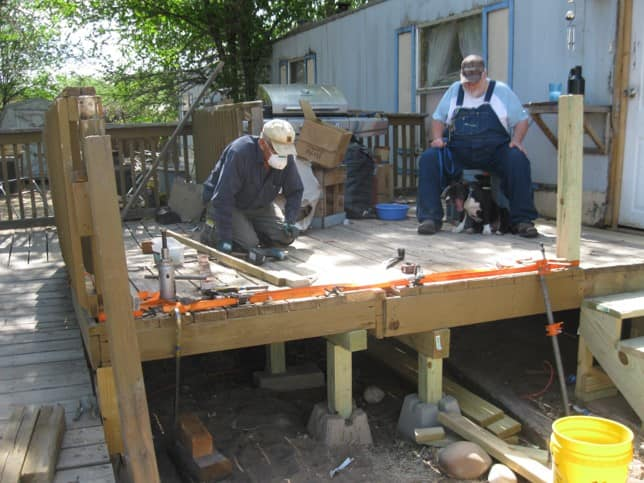 As homeowner Alan Martin and his dog Maggie watch, Tres Rios Habitat for Humanity volunteer Daniel Sedillo helps build a new porch for Martin and his wife this summer.