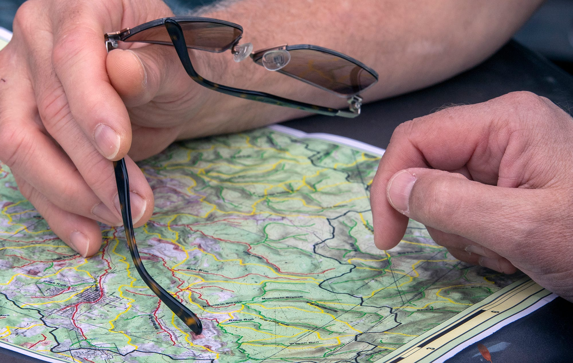 Eric Skrivseth and Eric Rosengrant study a topographical map of streams that were marked in the past as tainted with mine discharge. The red lines indicate creeks that have tested positive for mine discharge and the green lines are for those running clean.