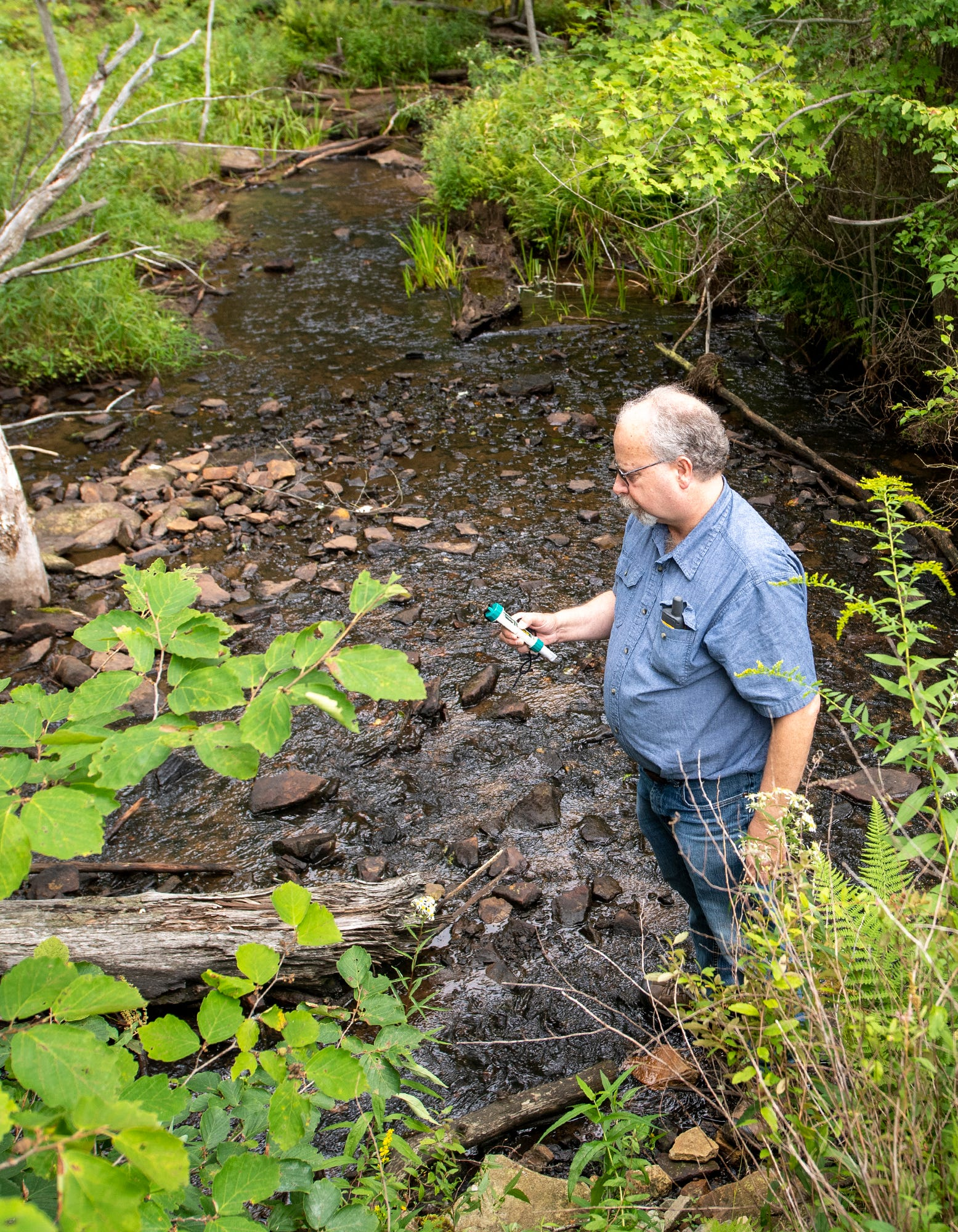 Eric Skrivseth, a retired railroad worker, tests mine discharge downstream after it was treated with limestone and holding ponds on August 30, 2020. In this case, treatment and dilution of other water sources has mitigated the effects of the mine discharge.