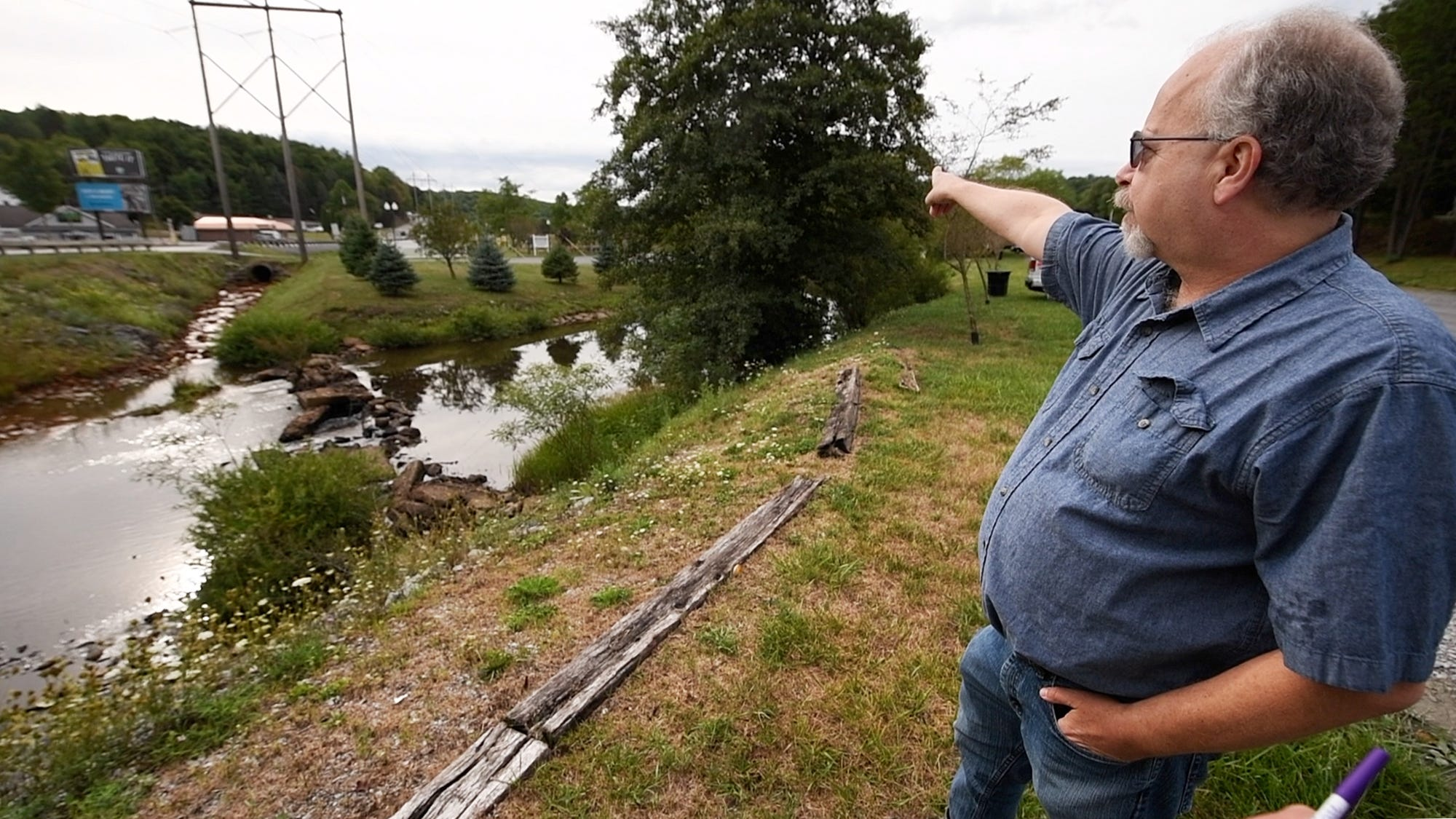 Eric Skrivseth points to a diversionary creek created to bring mine discharge two miles downstream from a recreation area in Philipsburg, Pa. Sept. 30, 2020.